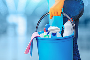 Woman Holding a Bucket With Cleaning Products