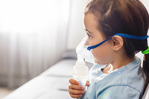Child With Asthma With a Respirator Mask