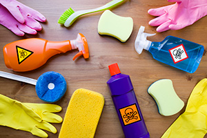 Cleaning Bottles With Toxic Labels Among Cleaning Gloves and Sponges